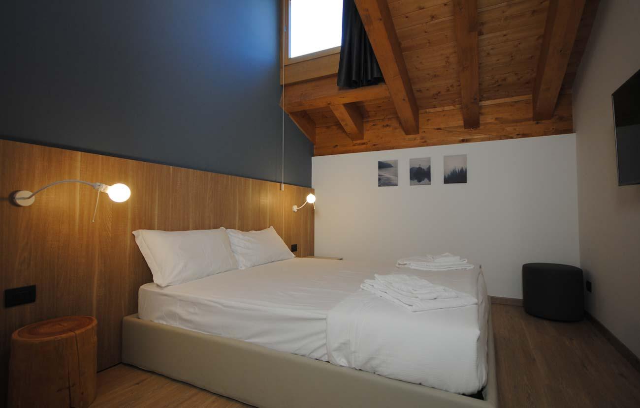 Camera da letto appartamento B&B, con letto matrimoniale, travi a vista e lucernaio