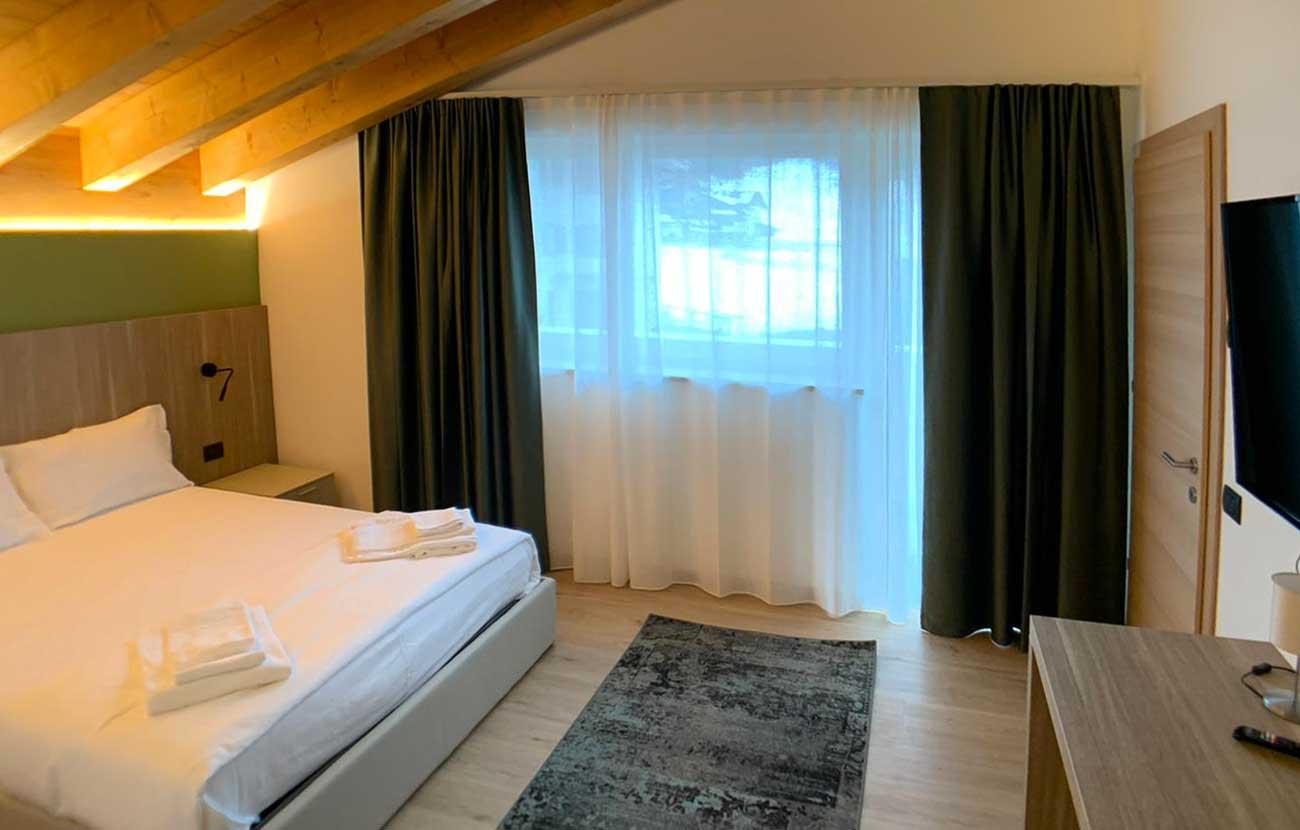 Camera da letto appartamento B&B con letto matrimoniale e grande finestra con tende