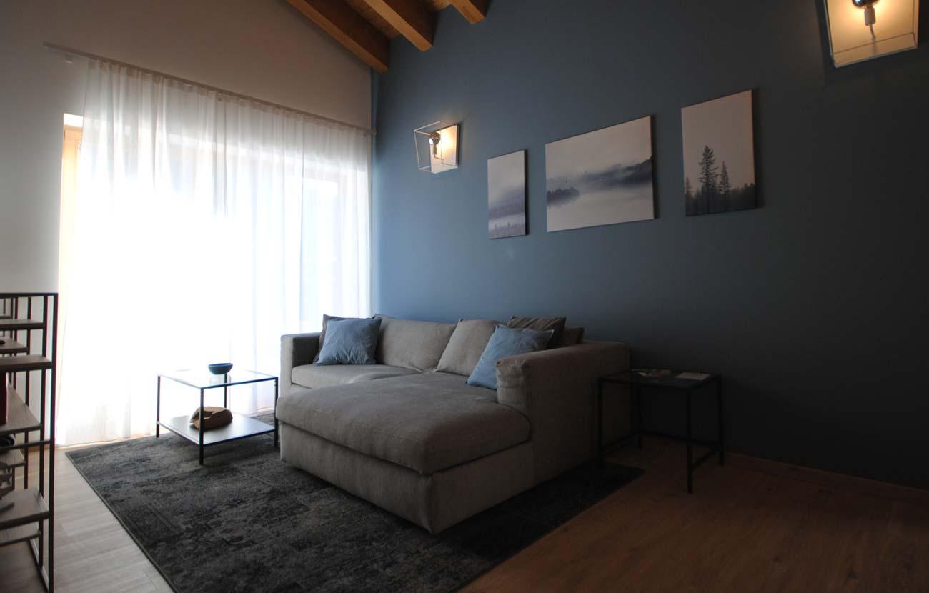 Salottino appartamento B&B con divano, pareti azzurre e una grande finestra