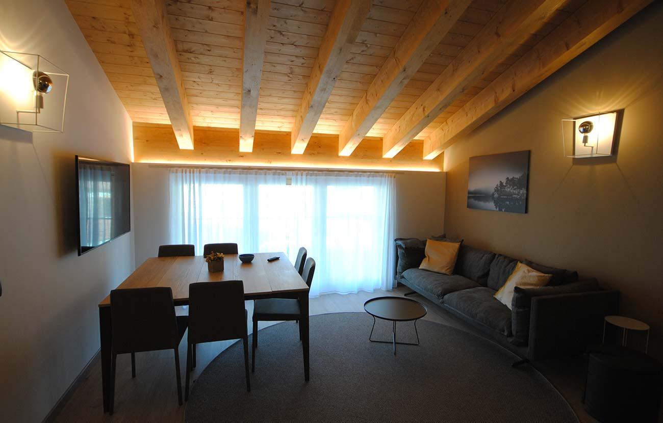 Salottino appartamento B&B con divano, tavolo e sedie e televisione alla parete
