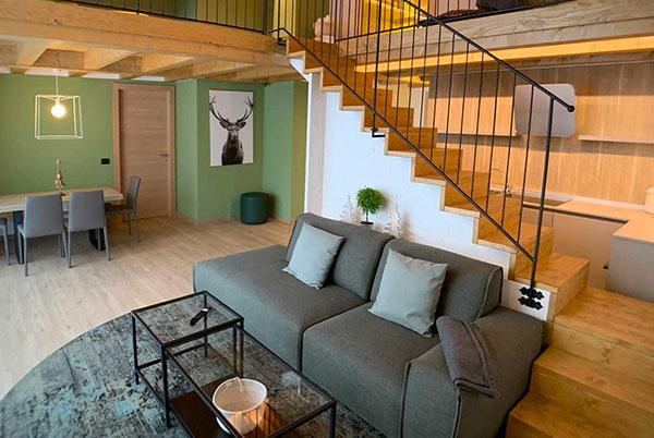 Ingresso appartamento B&B con elegante poltrona e tavolino su tappeto verde. Di fronte all'ingresso tavolo da pranzo con sedie