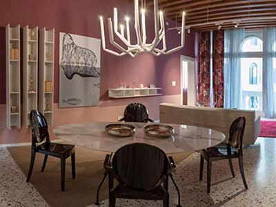 Elegante sala da pranzo di un palazzo a Venezia. Tavolo tondo con sedie, divano di fronte alle finestre