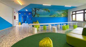 La scuola nel bosco piano estate. Sulla parete stampa di un paesaggio marino.